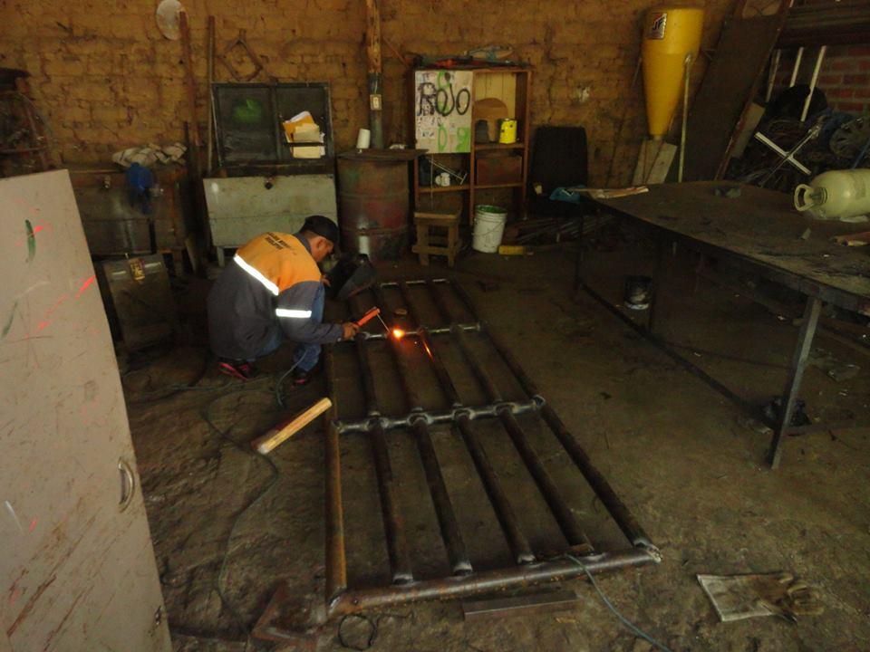 Personal de mantenimiento elaboran parrillas y tapaderas metálicas